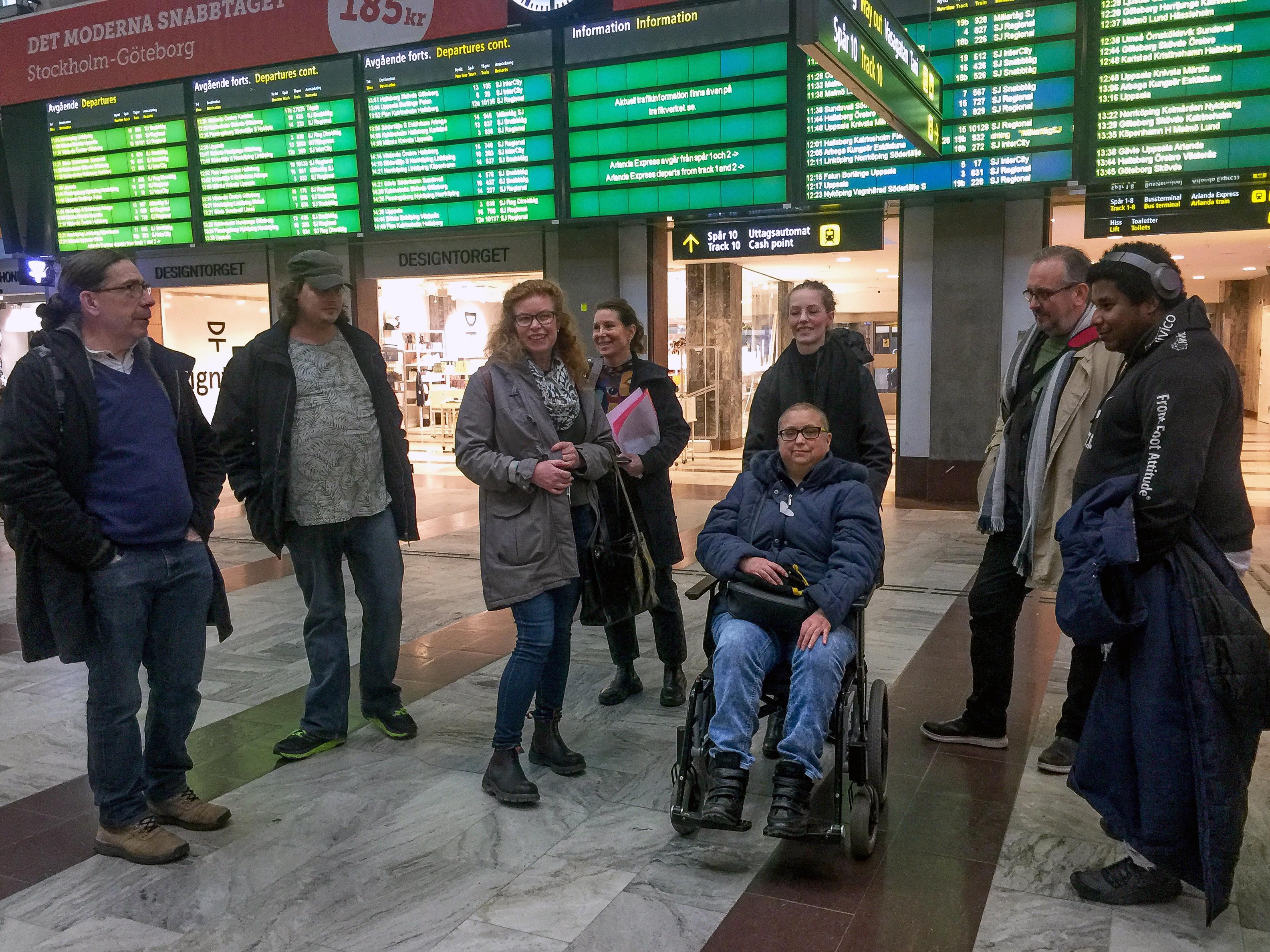 Deltagare från Begriplig text, Begripsam och Trafikverket nedanför den stora skylten med tåginformation i centralhallen.