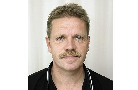 Bengt tittar rakt in i kameran och har en neutral bakgrund.