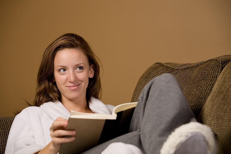 kvinna sitter i soffan och läser