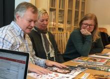 En man och två kvinnor sitter vid ett bord med tidningar och magasin. De tittar på omslagen.