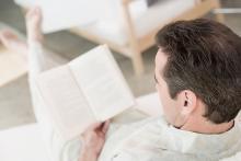 Bilden föreställer en man som läser en bok.