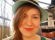 Bilden: En leende Anna Båve Schultz med hatt och långt hår i hästsvans.