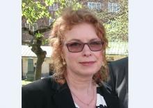 Bild på Camilla Ejdestig, medelålders kvinna med en rödlätt hår och solglasögon. Bilden är tagen utomhus.