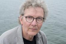 Bilden föreställer Karl-Einar Löfqvist. Han ser allvarlig ut. Han har kort hår, grå skjorta och bär runda glasögon.