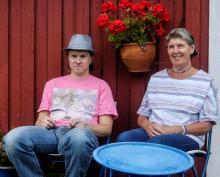 Bilden föreställer en ung vuxen man och hans mamma. De sitter utomhus på en varsin stol, framför en vägg av panel som är målad med falu rödfärg.