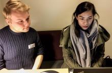 Två personer sitter bredvid varandra och tittar på en datorskärm.
