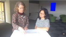 Skärmdump från video, två kvinnor står vid ett bord och samtalar