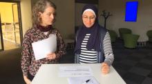 Skärmdump från video, på bilden står två kvinnor framför ett bord och samtalar