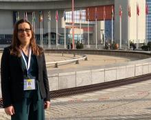 Bild på Ylva Bjelle framför FN-byggnaden i Wien.