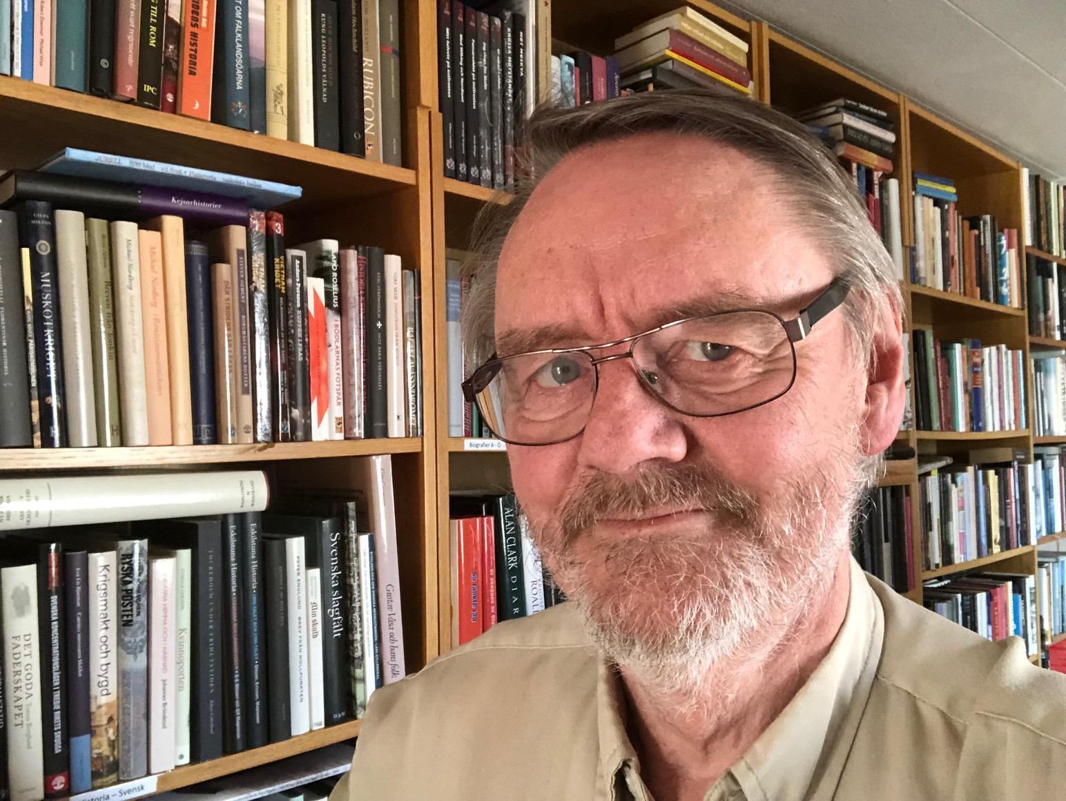 Torbjörn Lundgren framför bokhylla.